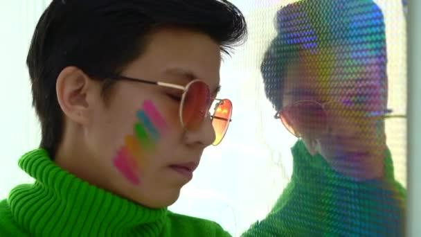 Barevné jiskřící odraz s asijskou LGBT žena podporu homosexuálních práv duha tvoří na tváři