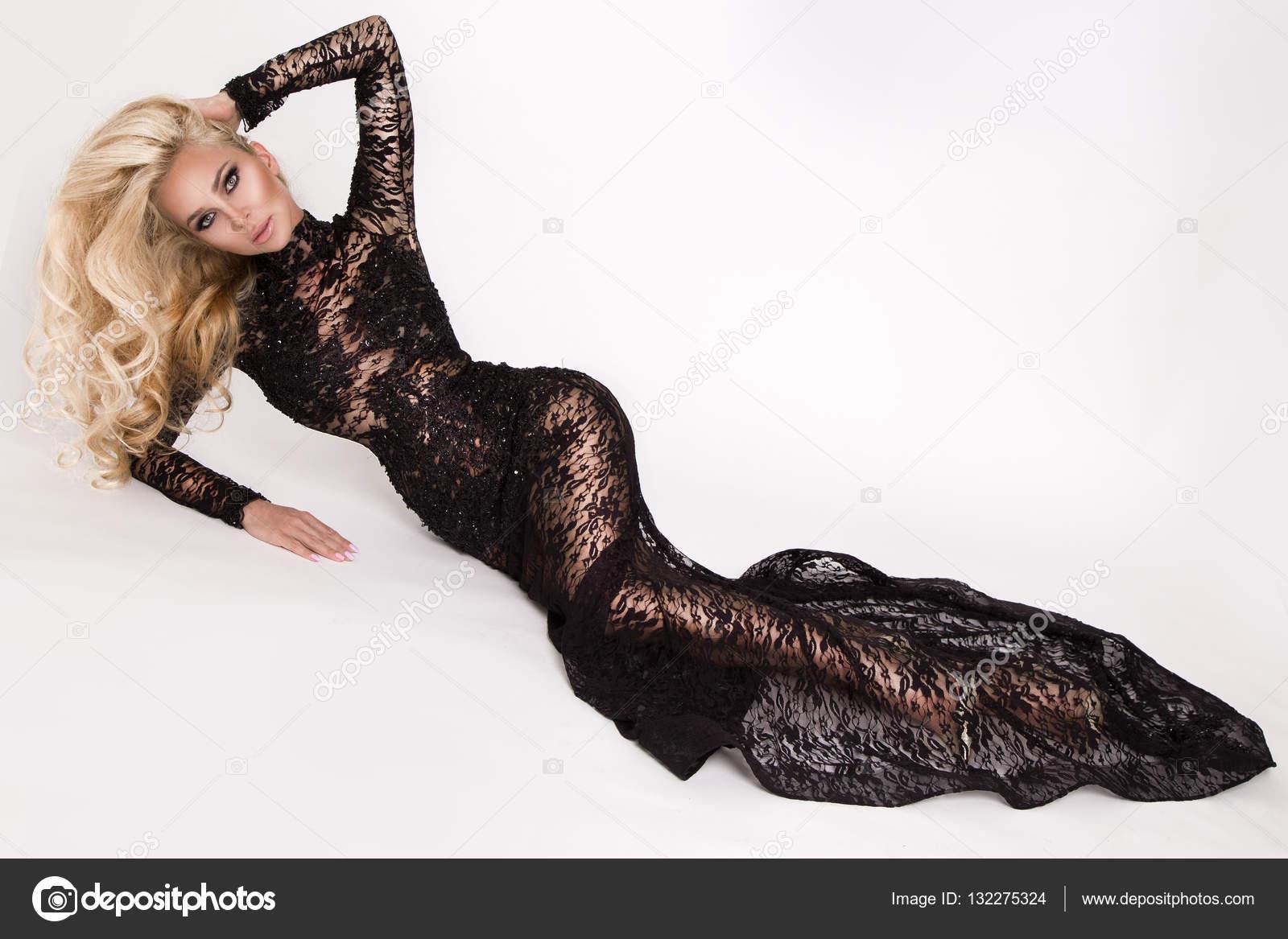 Bella bionda alta sottile con incredibile corpo vestito in un elegante vestito  di pizzo sorge su sfondo bianco e posa sensualmente — Foto di marcink3333 d5fea5c0fb6