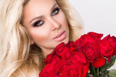 Portrait of the beautiful blonde woman and amazing looks and long hair, perfect skin, keeps the face of a bouquet of red roses flowers, valentine days