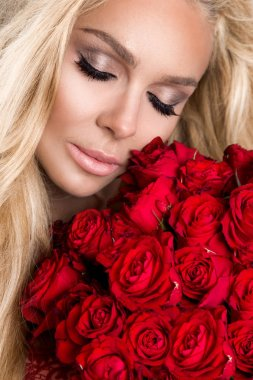 Beautiful sexy blonde woman and amazing looks and long hair, perfect skin, she hold bouquet of red roses flowers Valentine's Day