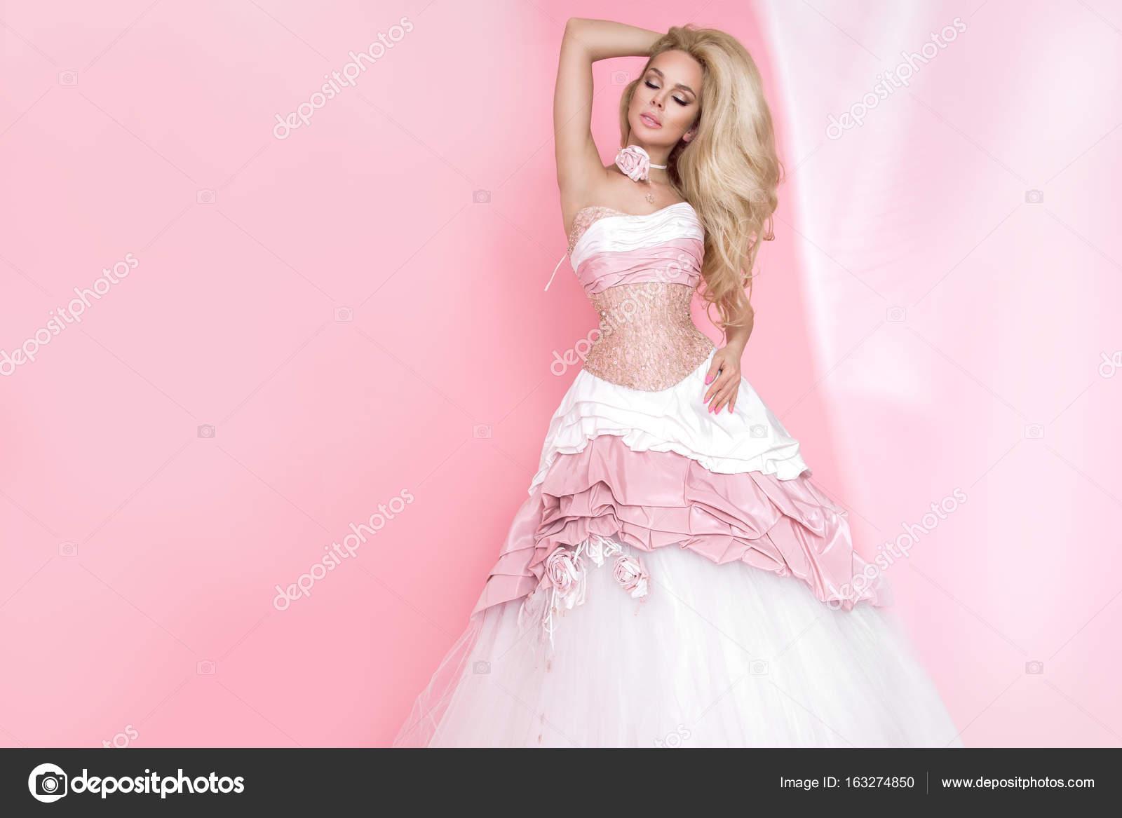 Modelo mujer rubia hermosa en un vestido de boda en un fondo rosa ...
