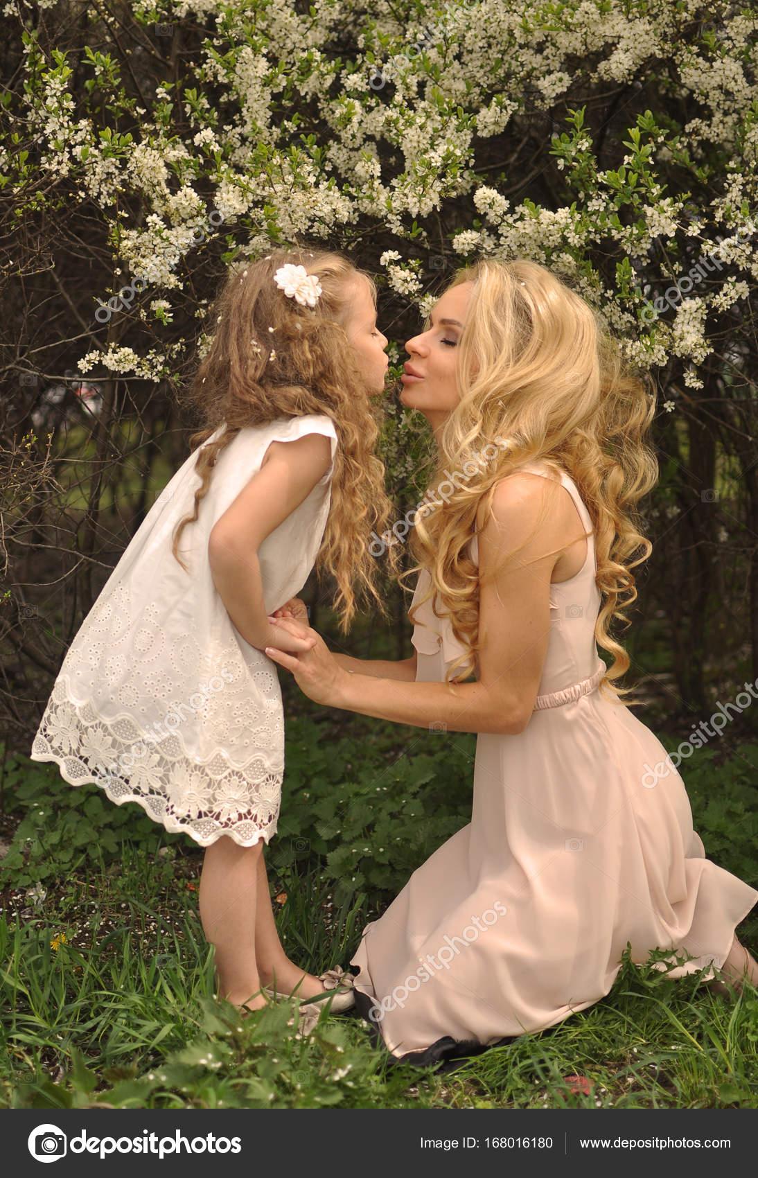 Schöne junge Mutter mit ihrer Tochter gekleidet im Frühling Kleidung ...