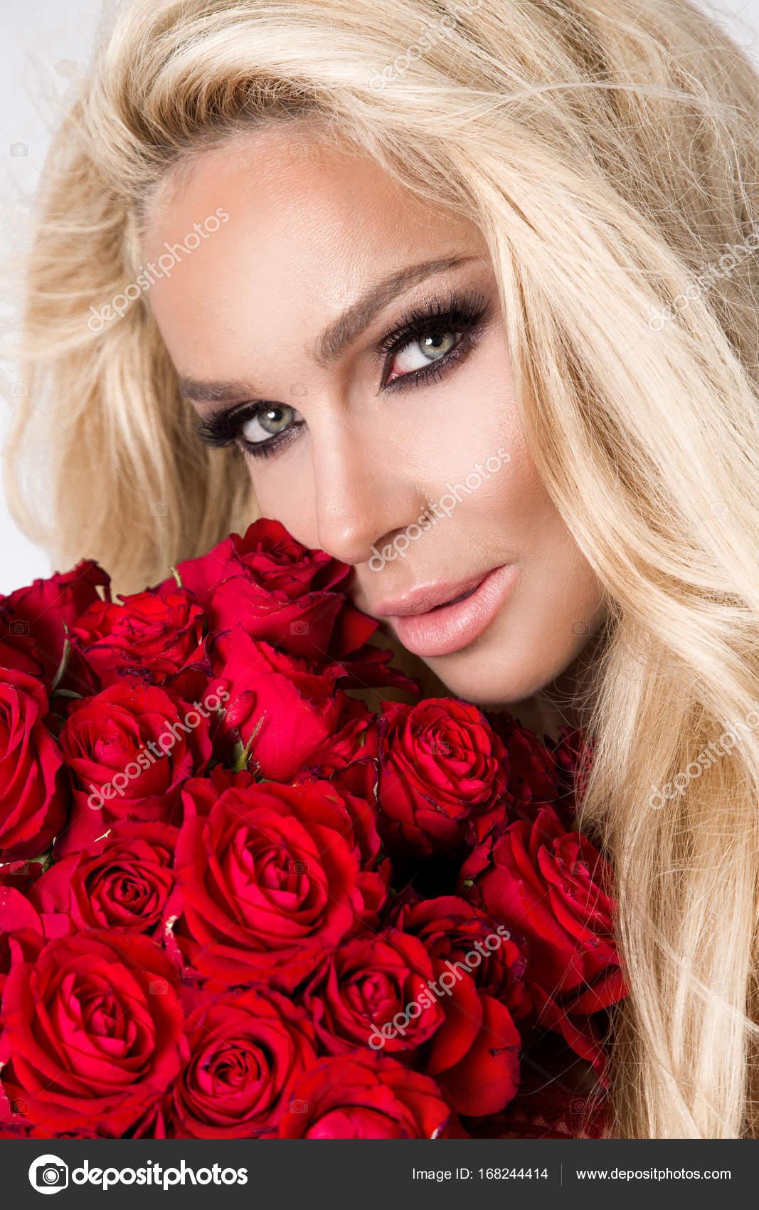 ecc668ef1468 Όμορφη σέξι ξανθιά σε κομψά εσώρουχα σε λευκό φόντο. Κορίτσι κρατώντας ένα  μπουκέτο κόκκινα τριαντάφυλλα