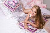 zierliche junge schöne blonde Mädchen, kleine Prinzessin mit langen Haaren und blauen Augen, das Kind liegt im Bett, schläft in Bettwäsche in Schmetterlingen und lächelt freudig