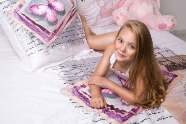 Gracious young beautiful blond girl, little princess with long hair and blue eyes, the child lies in bed, sleeping in linen in butterflies and joyfully smiles
