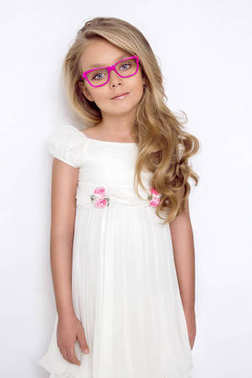 Cute little girl in a white communion dress, standing on a pink