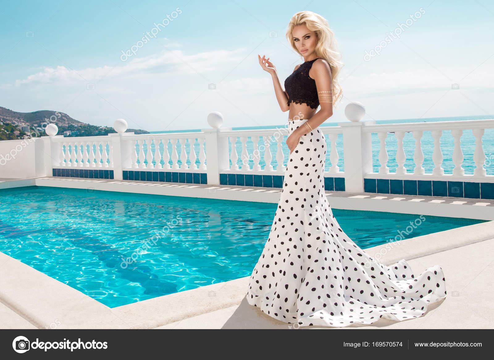 Schöne blonde weibliche Modell stehen neben einem exklusiven Pool in ...