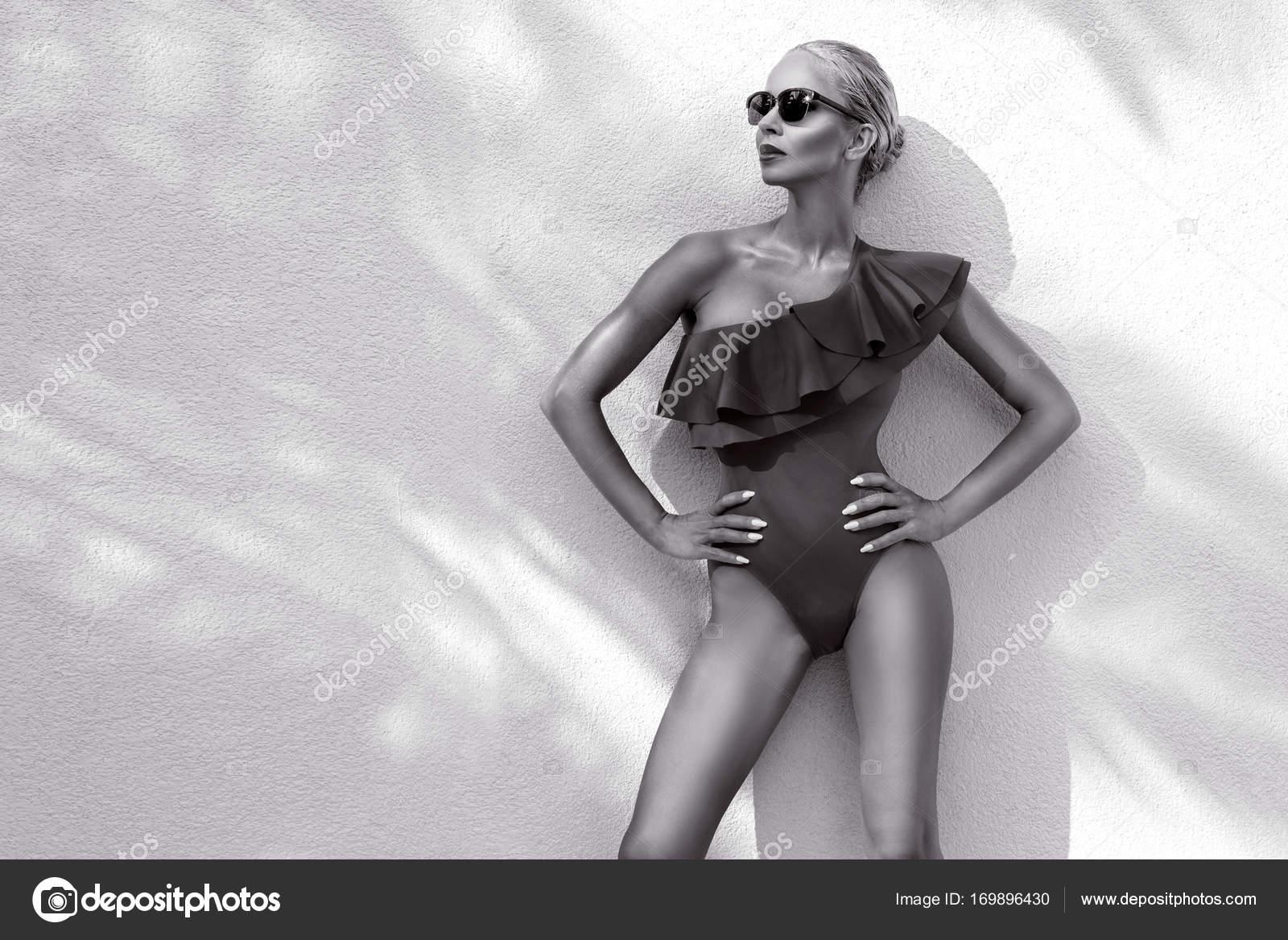 Beau portrait femme phénoménale d élégant modèle blonde sexy superbe avec  le visage parfait un lunettes de soleil se dresse avec élégant swinsuit sur  vue ... 500ad074621