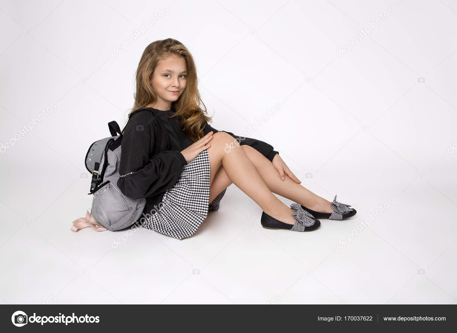 ec85a21b3907 Cute little girl dressed in school clothes and school backpack sitting on  white background– stock image