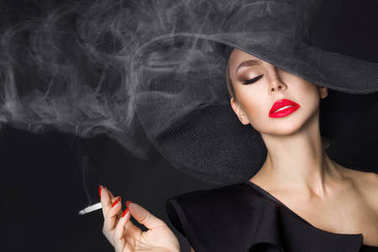 Elegant woman, femme fatale in black hat with cigarette in hand. On black background