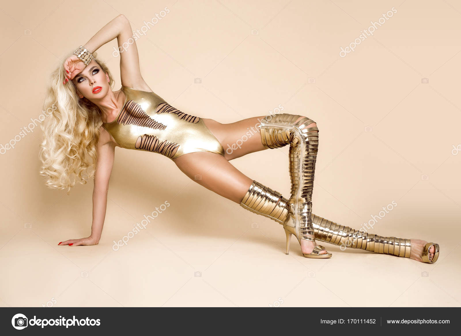 08bef901af6 Elegant woman in sexy bikini and amazing gold high heels shoes on a beige  background —