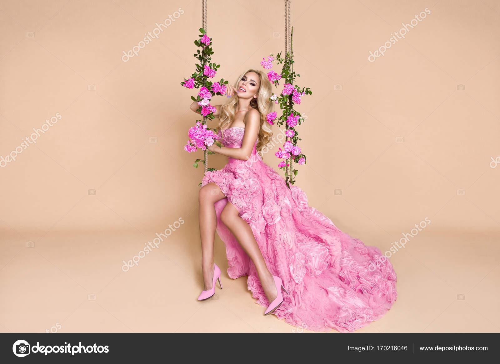 Novia rubia hermosa en un vestido de novia en un columpio decorado ...