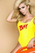 Fotografia Bagnino sexy con capelli biondi lunghi, in piedi in bikini e sensualmente in posa su sfondo beige