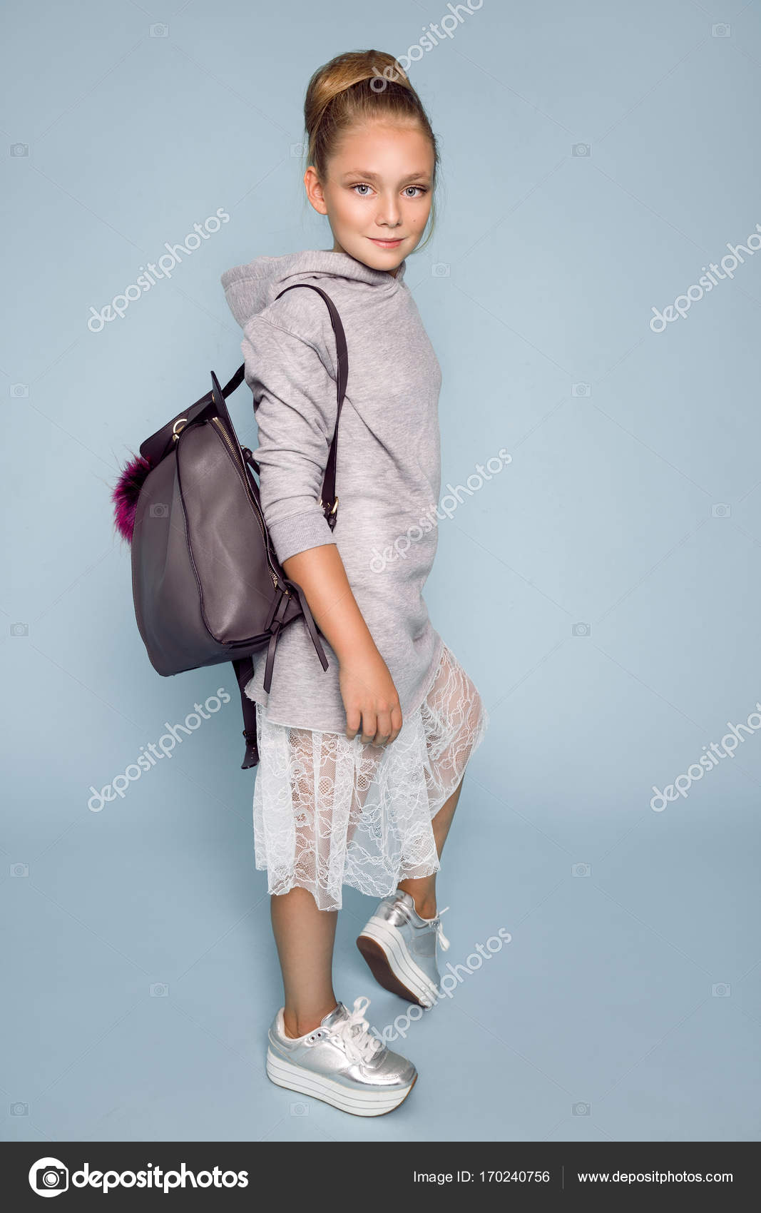 c81ea8968739 Cute little girl dressed in school clothes and school backpack standing on  blue background– stock image
