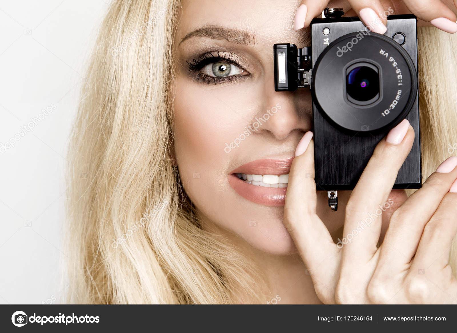 c07e8524fc2b Ξανθιά γυναίκα ομορφιά μοντέλο με εκπληκτικά μακριά μαλλιά και τέλειο  πρόσωπο θέτοντας σε λευκό φόντο και κρατώντας μια φωτογραφική μηχανή στο  πρόσωπό της ...