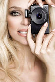 Beauty blonde female model with amazing long  hair and perfect face  posing on a white background and  holding a camera at her face and make photos