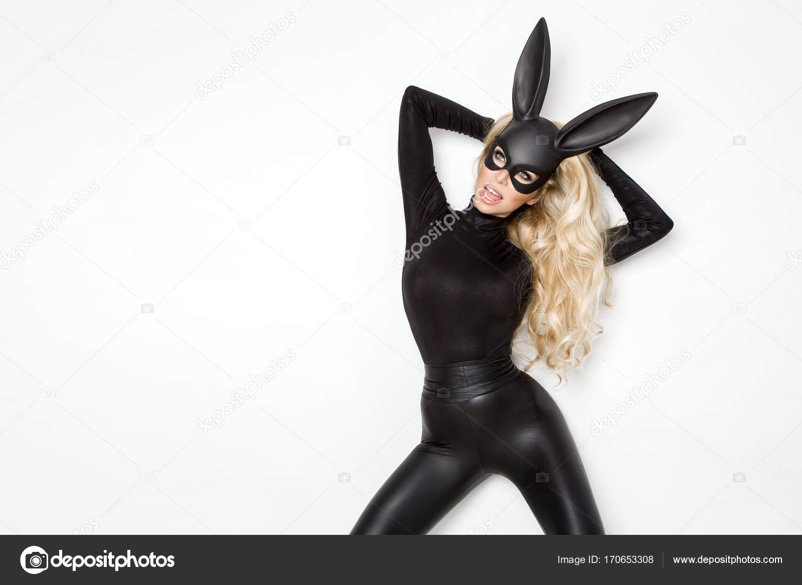 Beautiful young woman in Halloween, tattoo costume and black bunny mask,  standing on white background– stock image