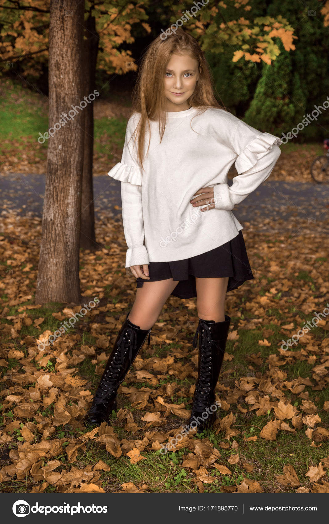 d7568ba008b9 Cute little girl dressed in coat and boots sitting on autumn background
