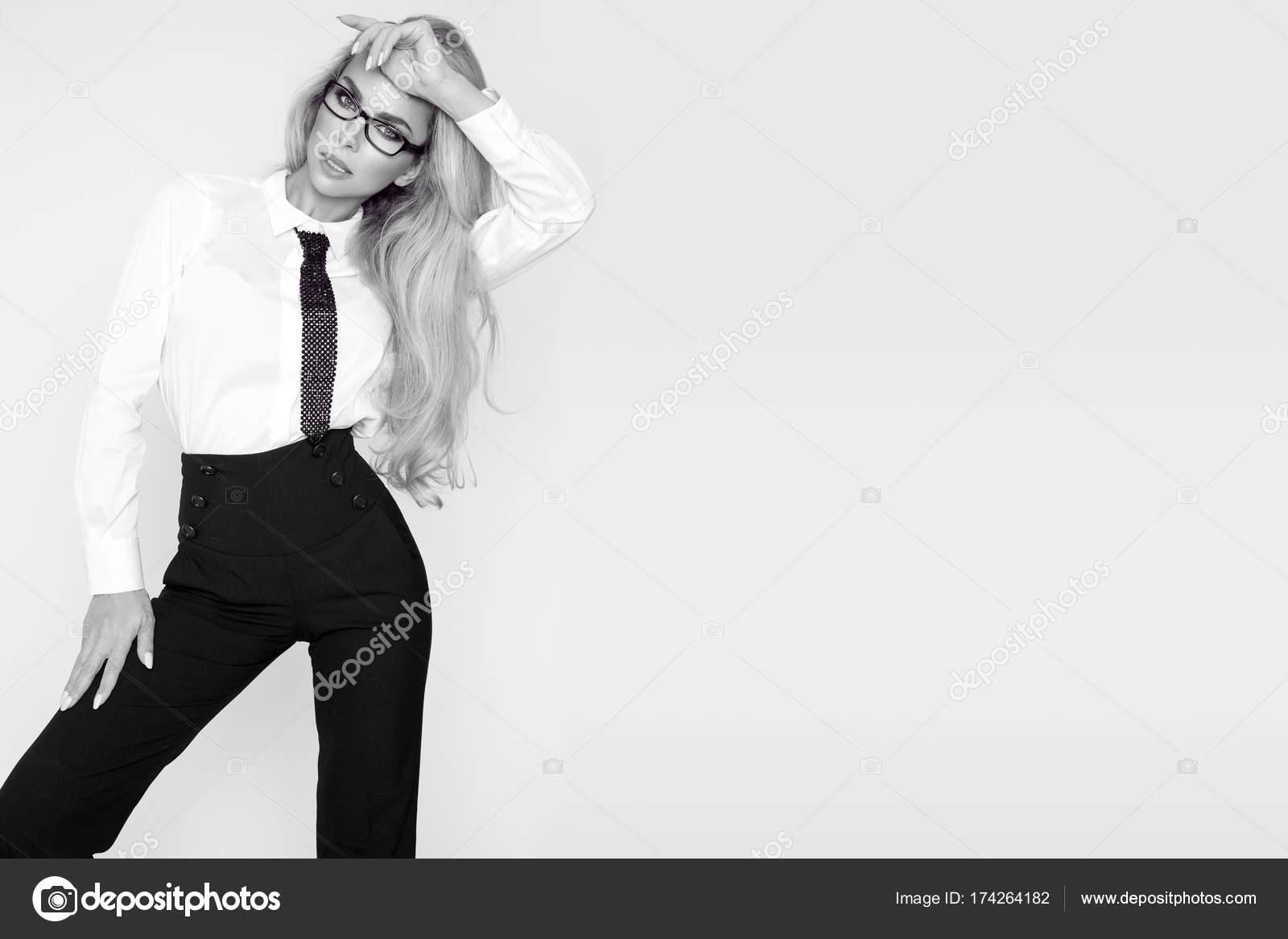 4cc1f42f70 Bella, elegante, sexy modella bionda vestita in camicia bianca e cravatta e  pantaloni neri. Sensuale donna d'affari con i vetri — Foto di marcink3333