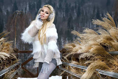 Beautiful young woman in winter clothing, standing on the snow and in the background has a beautiful view of the mountains.