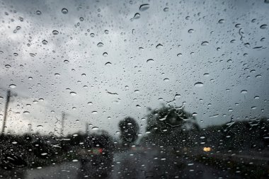 Raindrops on the car glass while driving through heavy rain and storm surges.