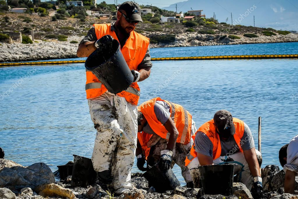 Workers try to clean up oil that has washed ashore, on a beach o