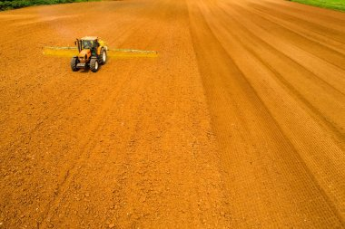 Aerial shot of  Farmer with a tractor on the agricultural field