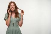 Portré boldog vörös hajú lány romantikus ruha néz félre, és széles körben mosolyog, beszél telefonon és csavaró haj az ujján, elszigetelt fehér háttér