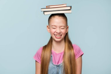 young schoolgirl with books. knowledge and learning concept. Back to school. blue background