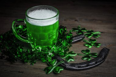 St. Patrick's Day. Green Beer pint with rusty horseshoe on wooden table, decorated with shamrock leaves. Glass of Green beer close-up. Selective focus. Blurred background.