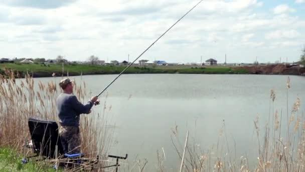 Rybář z břehu jezera rybaří. Výstřel naslepo. Slunečný den. Village