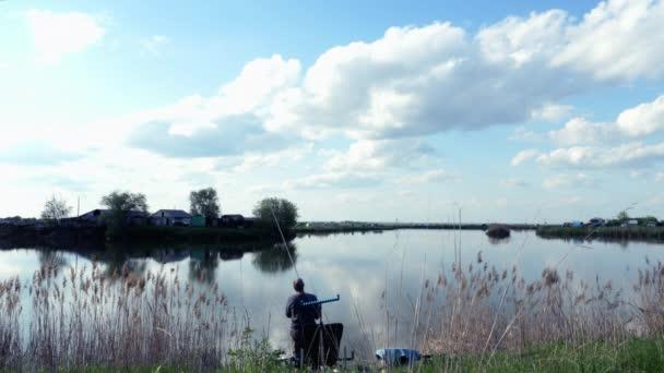 A magányos fiatal halász bedobja a horgászbotot a tóba. Visszanézni. Távolról sem..