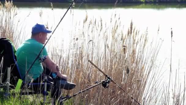 Oldalnézetből. Halászok ülnek egy széken a bokros fű partján tó és a halászat
