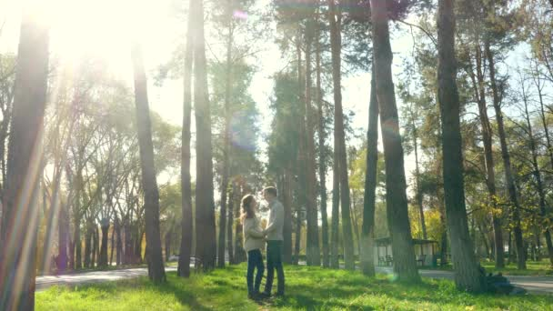 couple in love stands in the park and hugs in same clothes. Sun light, big trees