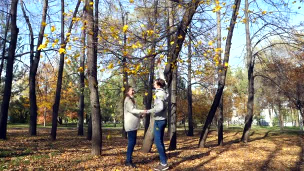 pregnant woman and her husband kiss under a tree in the fall autumn slow motion