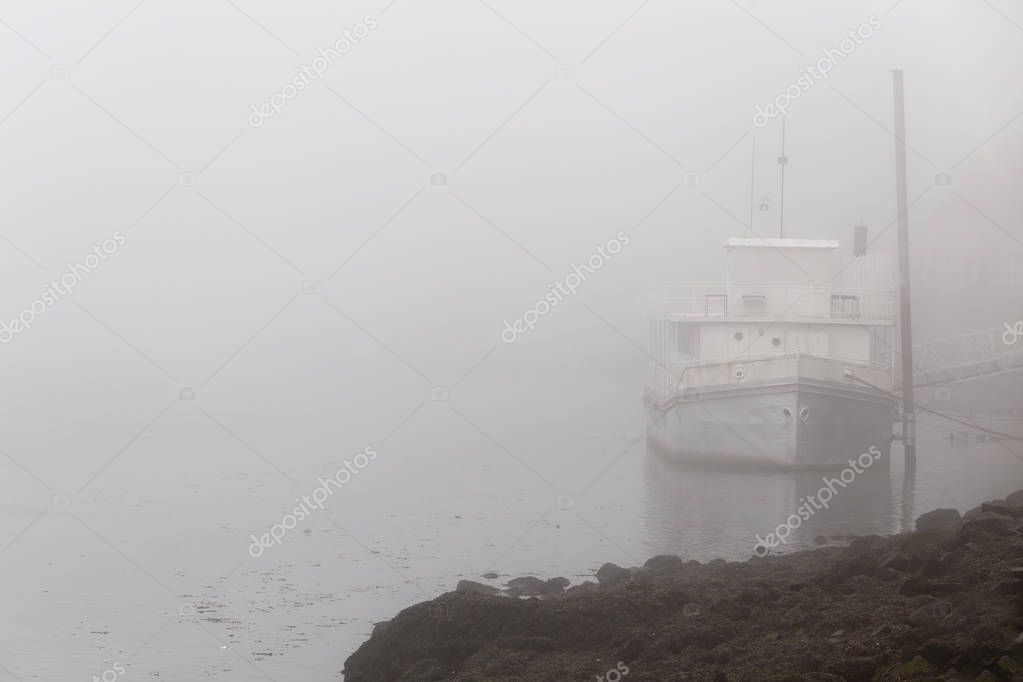 Old river boat in a foggy morning