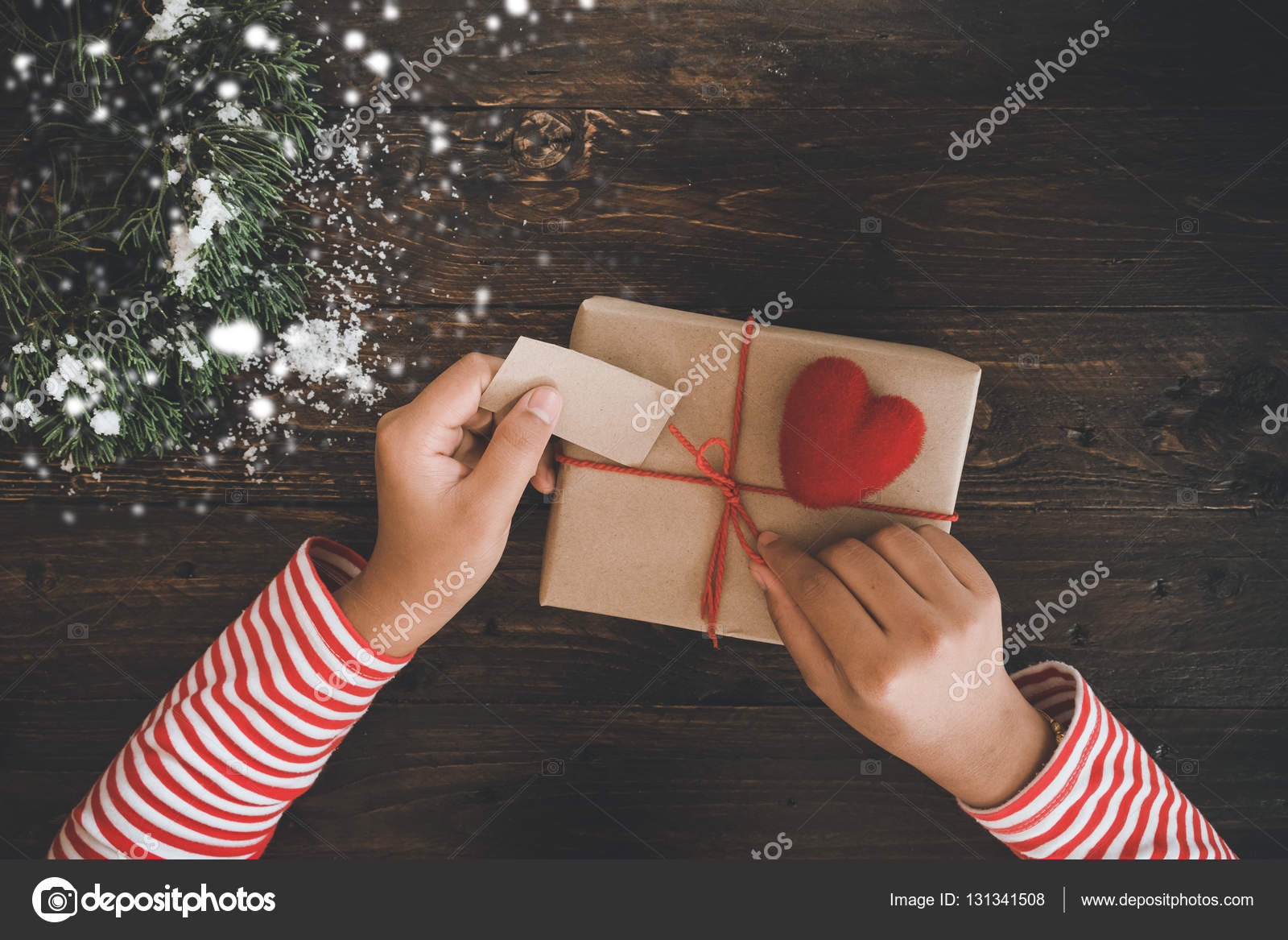 Frau Hände halten ein Weihnachtsgeschenk mit einem roten Band ...