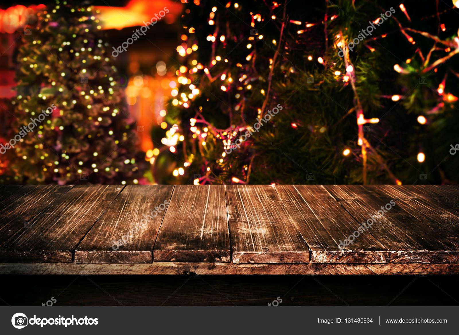 Christmas And New Year Background With Empty Dark Wooden Deck Table Over Tree Blurred Light Bokeh Display For Product Montage