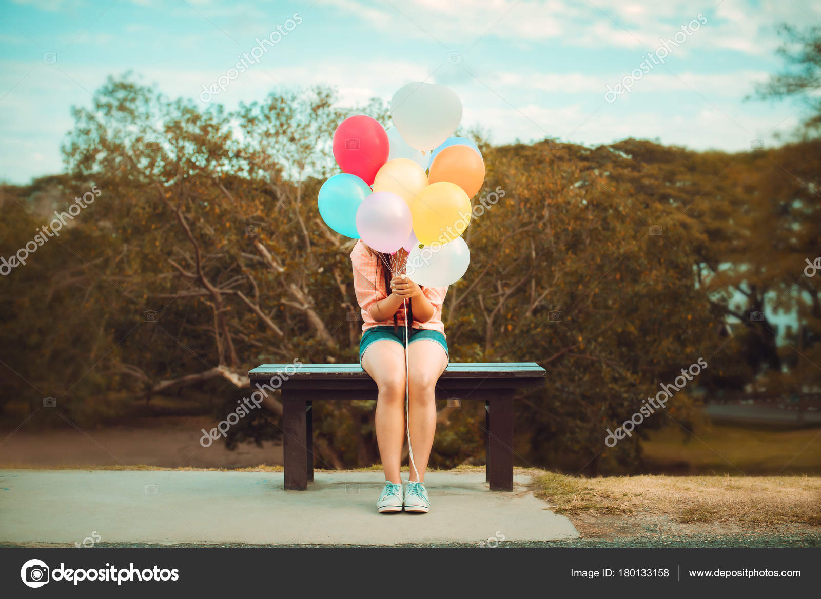girl hand holding multicolor balloons done retro instagram