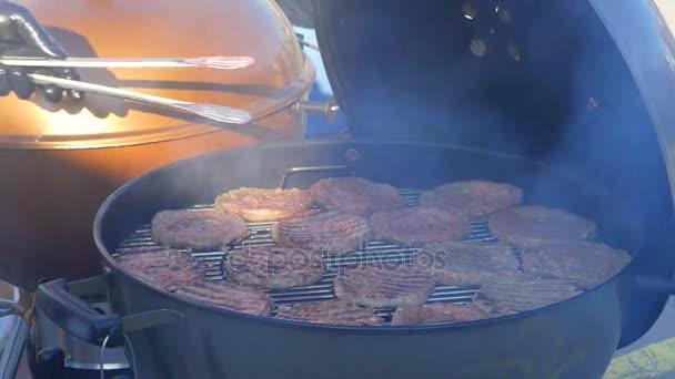Kuchař se změní kotlety na grilu, kontroluje jejich připravenost