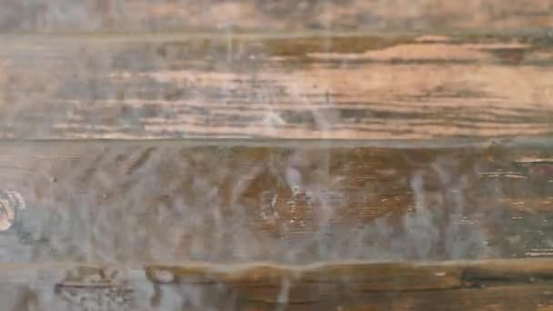 kapky vody bušila dřevěný povrch. Zpomalený pohyb.
