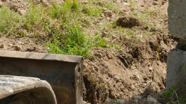 Bagr na housenky se pohybuje a čistí zem
