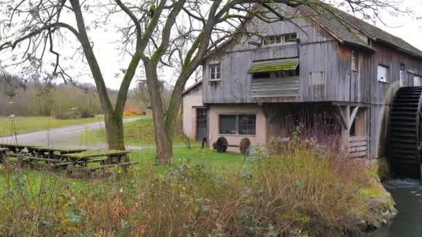 Front of old wooden mill with blade wheel in autumn countryside