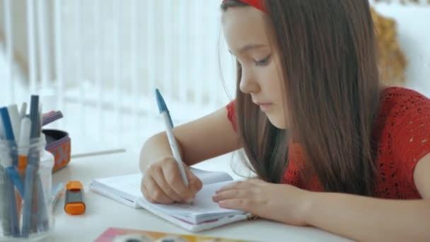 Krásná dívka v červené pečlivě píše a pero do svého deníku