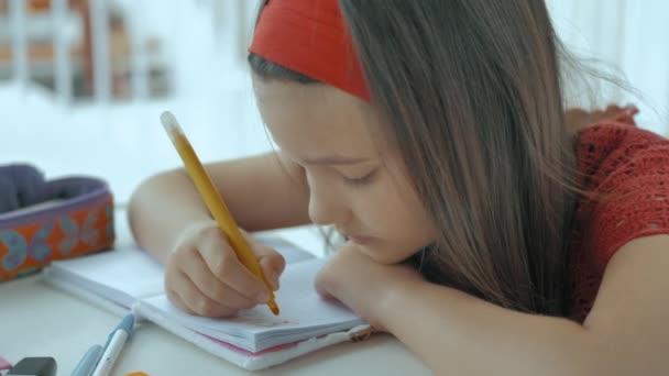mladý muž s hlavou na stole píše domácí úkoly