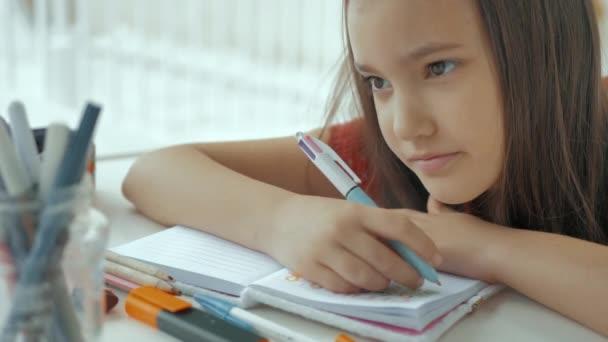 Pozorná a pozorná dívka píše do svého zápisníku