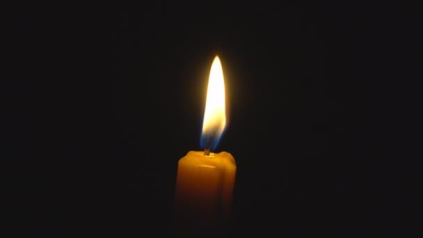 Kerzenfeuer auf schwarzem Hintergrund Mittelrahmen. Schwaches Licht und dramatische Szene. 4k 3840x2160 hohe Auflösung.