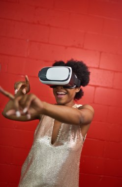 Cool millennial black woman exploring space with virtual reality glasses by a red concrete wall