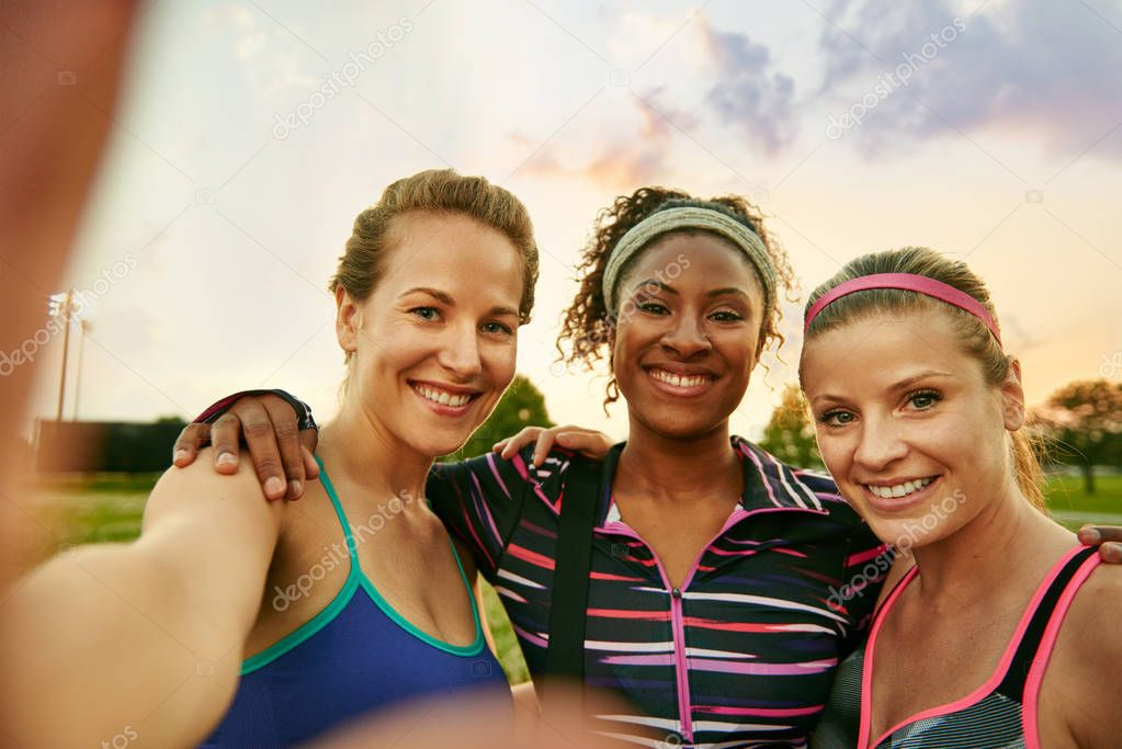 Diverse yoga class of three cheerful millennial women takes a selfie at sunset in nature park