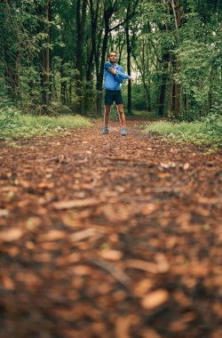 Fit male jogger stretches during day training for cross country forest trail race in a nature park.